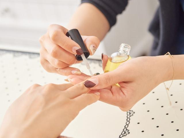 お客様の指にネイルオイルを塗るネイリスト