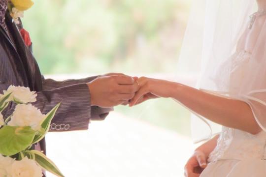 結婚式で新婦に結婚指輪をはめる新郎